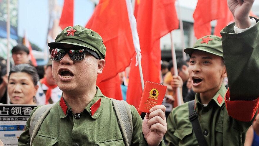 Protesters dressed as Chinese Red Guards chant during a May demonstration in Tsim Sha Tsui, Hong Kong. People from Hong Kong staged a satirical rally to urge Chinese tourists to stay in mainland China. Competition for housing, grades and jobs between the two groups have produced deep tensions.