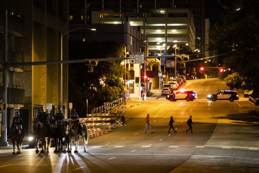 The area around Austin Police headquarters is closed off as protesters demonstrate outside the building Friday.