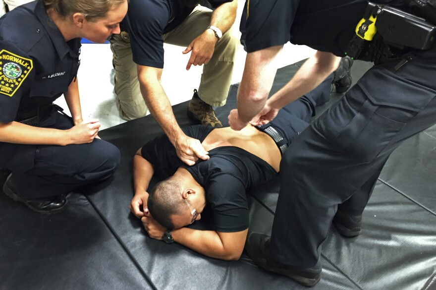 Police trainers place bandages on Officer Edgar Gonzalez's back after removing Taser prongs. He was Tased as part of his training at Norwalk Police Department's headquarters in Norwalk, Conn.