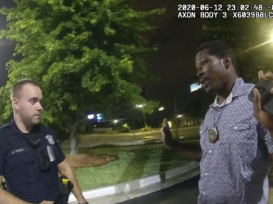 This screen grab taken from body camera video provided by the Atlanta Police Department shows Rayshard Brooks speaking with Officer Garrett Rolfe in the parking lot of a Wendy's restaurant on June 12 in Atlanta. Rolfe has been fired following the fatal shooting of Brooks, and a second officer has been placed on administrative duty.