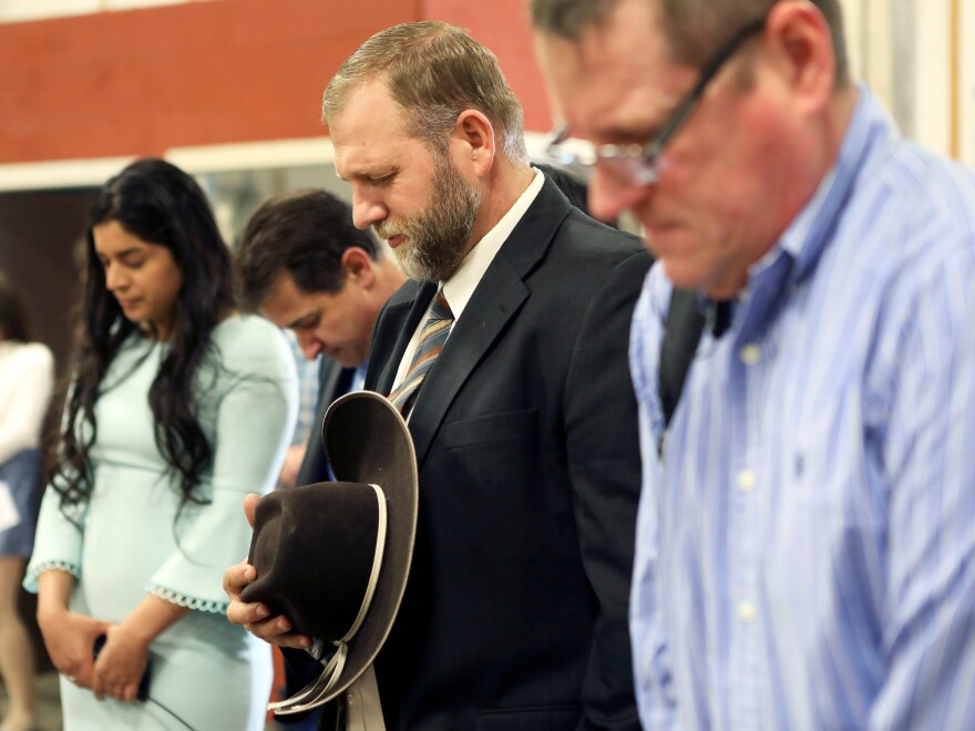 Libertarian activist Ammon Bundy (second from right) prays during an Easter Sunday church service he organized despite concerns over the coronavirus outbreak in Emmett, Idaho.