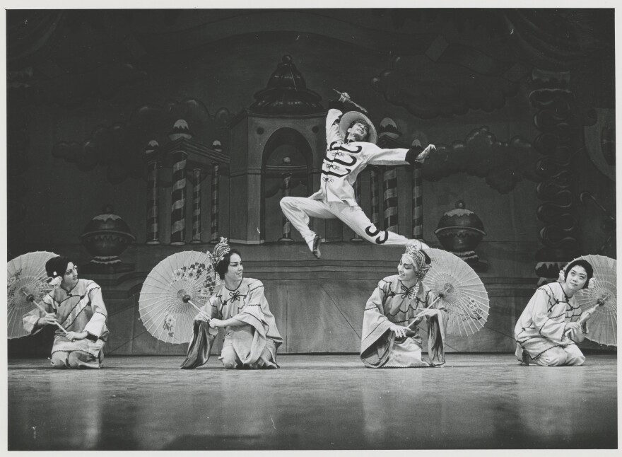 Photo of dancer leaping over costumed dancers with umbrellas.