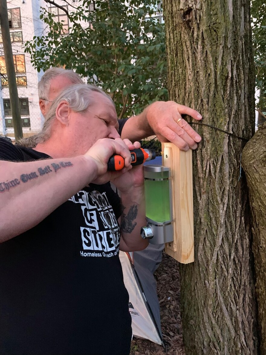 Watchmen of the Streets volunteer Todd Miller installs a hand sanitizer dispenser at a homeless camp east of uptown.