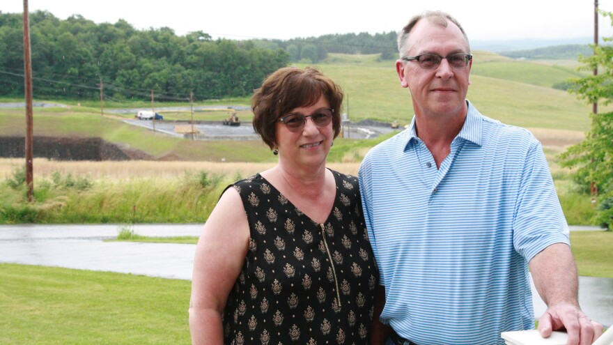 Mary Jo and Mike Picklo stand in their front yard in Somerset County, Pa. Behind them is the Acosta Deep Mine.