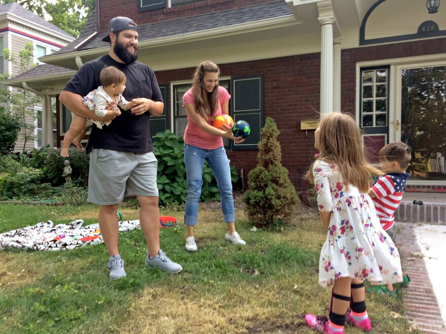 Entrepreneur Stinson Dean (left) and his wife Stephanie play with their three children in their yard in Independence, Mo.  He says the Affordable Care Act made it possible for him to start his own business.