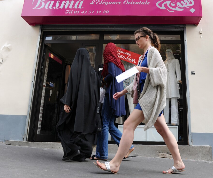 Three women, two of them partially veiled, walk past a hijabs shop in Paris. The wearing of the veil has been a serious point of contention in France, with the government banning its use in public schools and the wearing of face-covering garments, including burqas and niqabs, in public.
