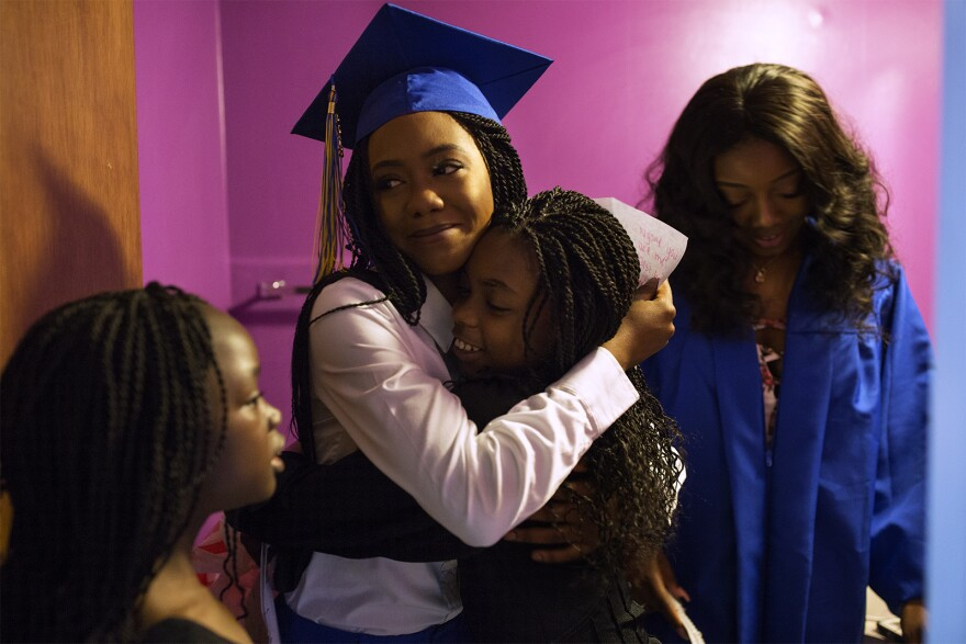 Ngone Seck hugs her younger sisters after opening graduation presents from them while getting ready for the ceremony. May 2018