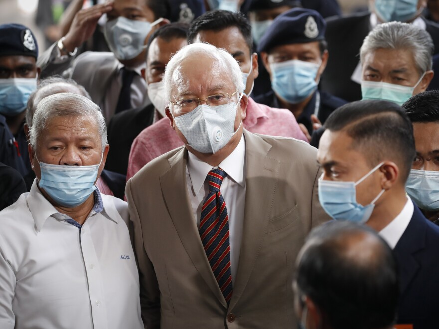 Former Malaysian Prime Minister Najib Razak, center, wearing a face mask with his supporters, arrives at the courthouse in Kuala Lumpur, Malaysia, on Tuesday. Najib was found guilty of corruption in the first of several trials linked to the multibillion-dollar looting of the 1MDB state investment fund.