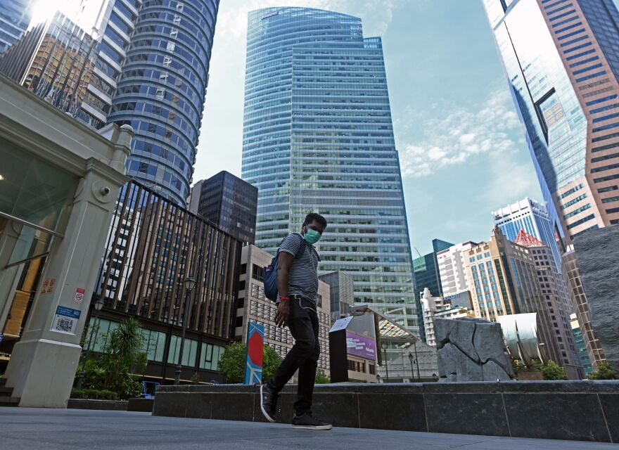 A man wearing a face mask as a preventive measure against the spread of the new coronavirus walks next to commercial buildings in the Raffles Place financial business district in Singapore on April 14.