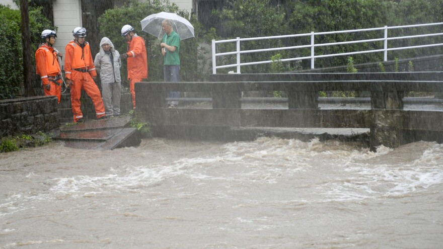 Rescue workers and local residents watch the Wada River, which has been swollen due to heavy rain in Kagoshima, Japan. More than a million people in southwestern Japan are under evacuation orders due to torrential rains.