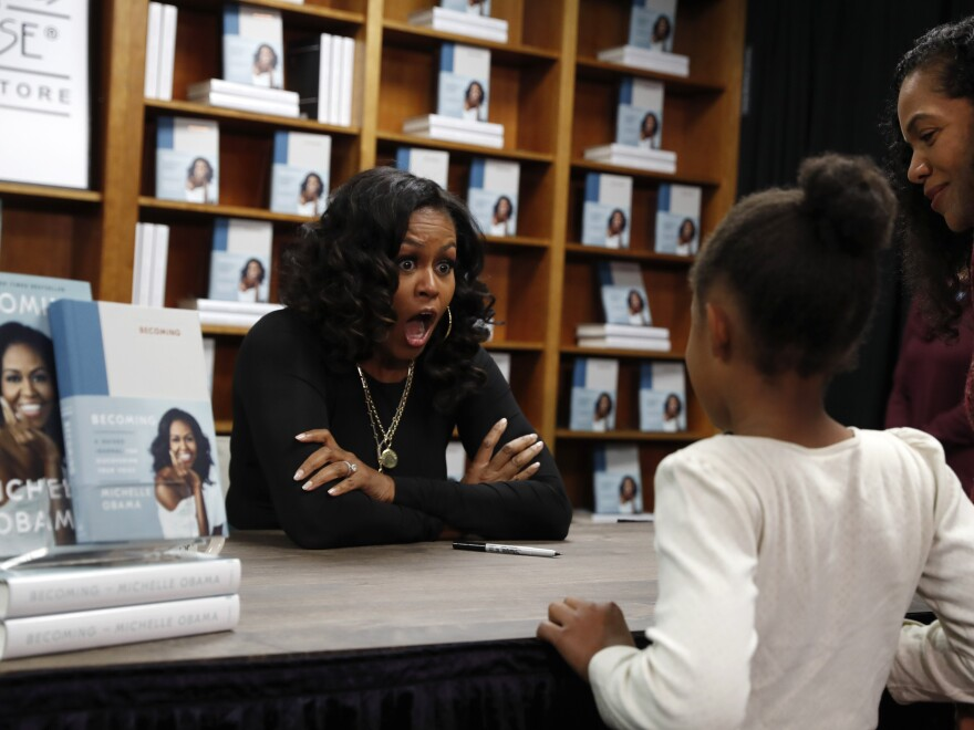 Michelle Obama reacts as Kaitlyn Saunders, 8, tells Obama that she is a competitive figure skater. Kaitlyn and her mother, Katrice Saunders, were buying signed copies of Obama's memoir, <em>Becoming</em>, last year at Politics and Prose bookstore in Washington.