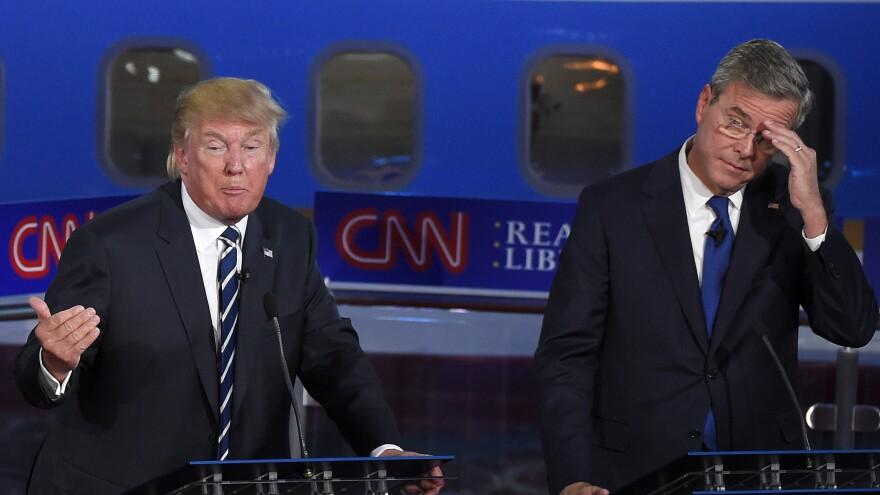 Republican presidential candidates Donald Trump, left speaks at a Republican presidential debate last month, as former Florida Gov. Jeb Bush listens.