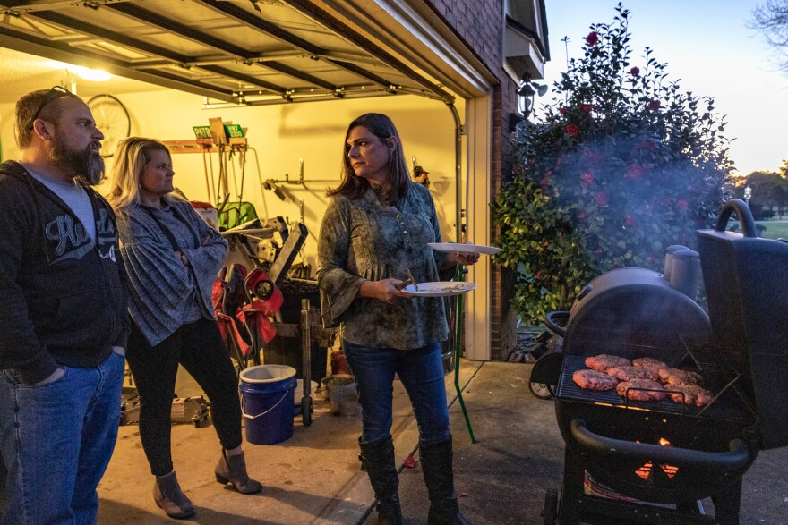 Lange grills burgers for friends Mike Balducci and Heather Buchanon-Romano at home.