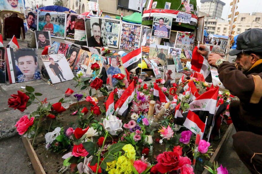 An Iraqi protester places his national flag on a shrine dedicated to those killed during the unrest, at Baghdad's Tahrir Square on Jan. 29.