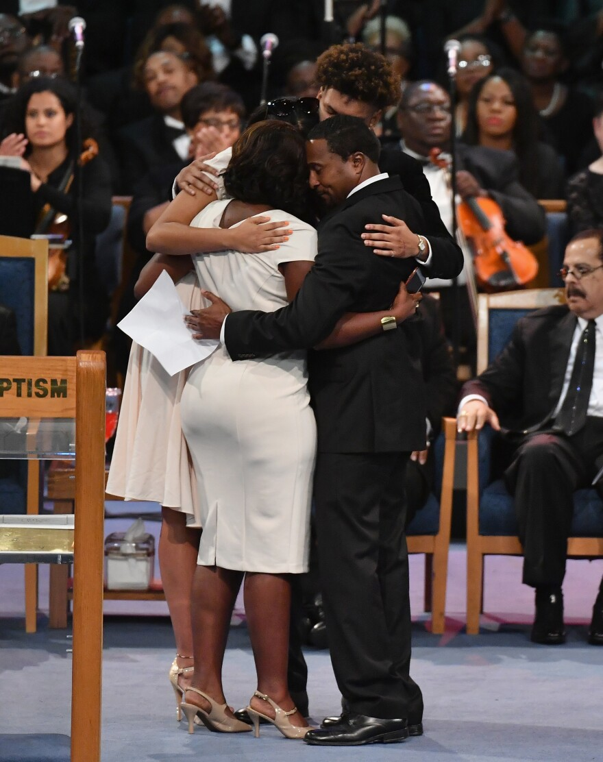 Members of Aretha Franklin's family embrace during the funeral. They took turns at the lectern to share stories of the late singer's life.
