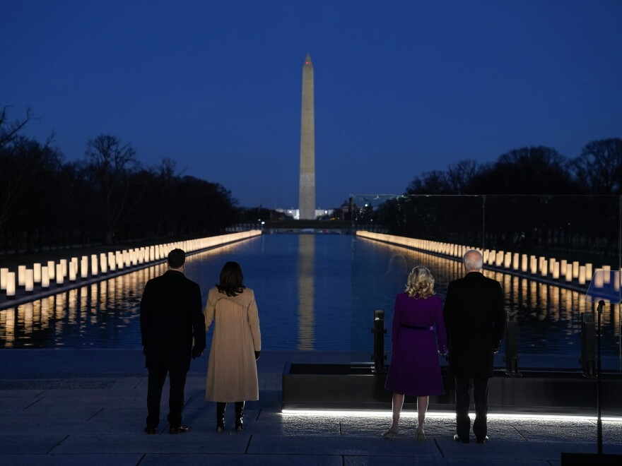 """With the Washington Monument in the background, President-elect Joe Biden with his wife, Jill Biden, and Vice President-elect Kamala Harris with her husband, Doug Emhoff, listen Tuesday as Yolanda Adams sings """"Hallelujah."""""""