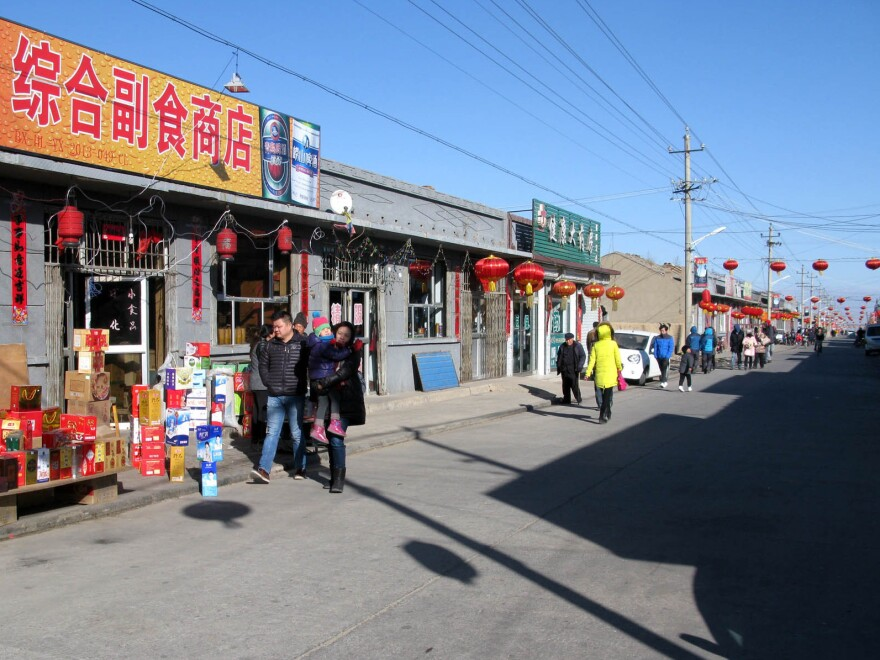 Tourists walk along a main thoroughfare in Nuanquan Town. While Lunar New Year festivities in China's cities have become highly commercialized and must compete with other, more modern diversions, folk customs in China's countryside remain vibrant.
