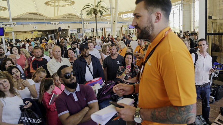 An EasyJet agent talks to tourists stranded at Sharm el-Sheik's airport in Egypt Friday. The airline's plans to operate at least 10 flights out of the resort today were hampered by delays.