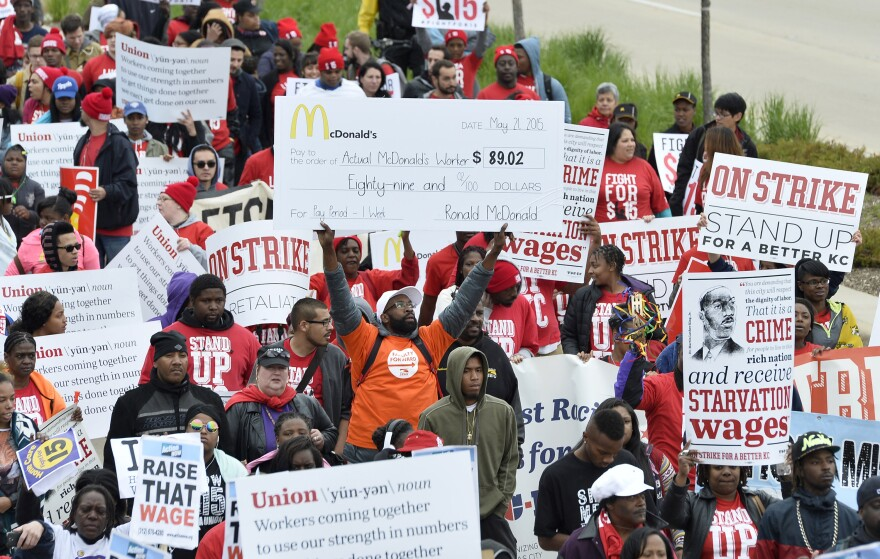 Demonstrators march on McDonald's corporate headquarters in Oak Brook, Ill., on Wednesday, demanding a wage increase to $15 per hour.