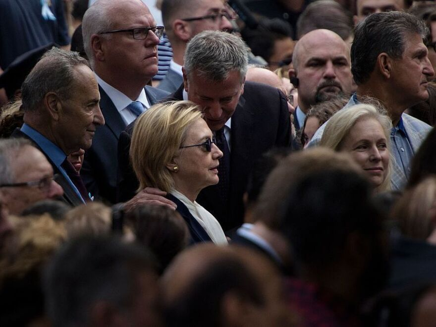 New York City Mayor Bill de Blasio speaks to Democratic presidential nominee Hillary Clinton during a memorial service at the National September 11 Memorial and Museum.