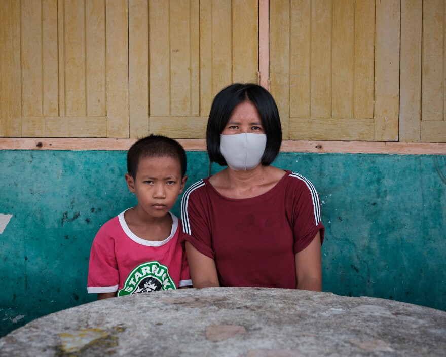 Pranee Thermuangpak, 38, with one of her three children. Pranee's husband, Samart Thermuangpak, a construction worker, tried to kill himself after his application for the 5,000 baht in government aid was denied. Pranee is epileptic and unable to work; her mother needs regular medication.