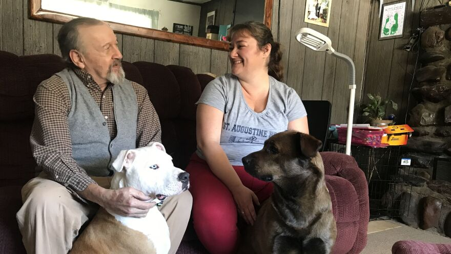 David Calderwood and Crystal Abel of Newport, Vt., sit with Abel's dogs Mike (left) and Zoe. David lives in Crystal's house, and she helps him with his medications and medical needs. He pays room and board, and Abel is also compensated by the state with Medicaid dollars.