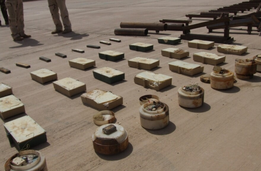 "U.S. and Iraqi soldiers display ""sticky IEDs""  — magnetic bombs that militants attach to vehicles — found during a raid at a checkpoint near the Iraq-Iran border."