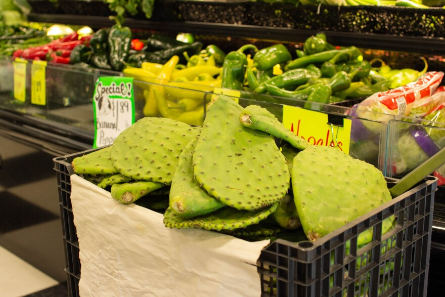 A crate of nopales cactus leaves sits among other produce in a grocery store.