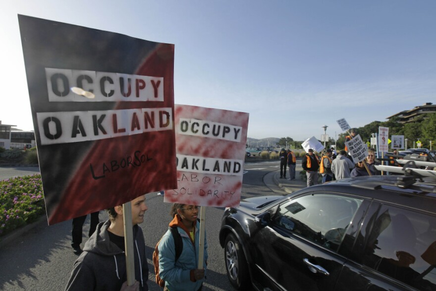 Two members of Occupy Oakland join striking Golden Gate Bridge, bus and ferry workers at the Larkspur Ferry Terminal in Larkspur, Calif on Tuesday.
