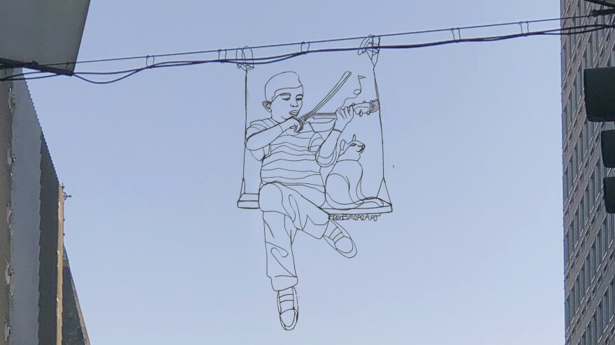 A wire sculpture of a man playing the violin for a cat hangs between two buildings against the backdrop of a blue sky.