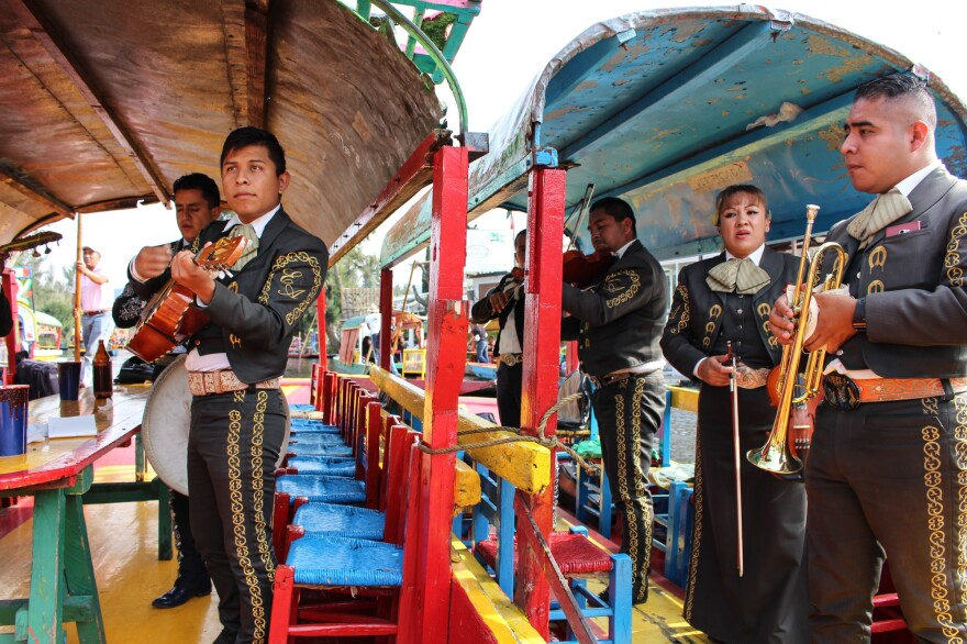 A mariachi band waiting to perform songs of your choosing from their <em>trajineras</em>.