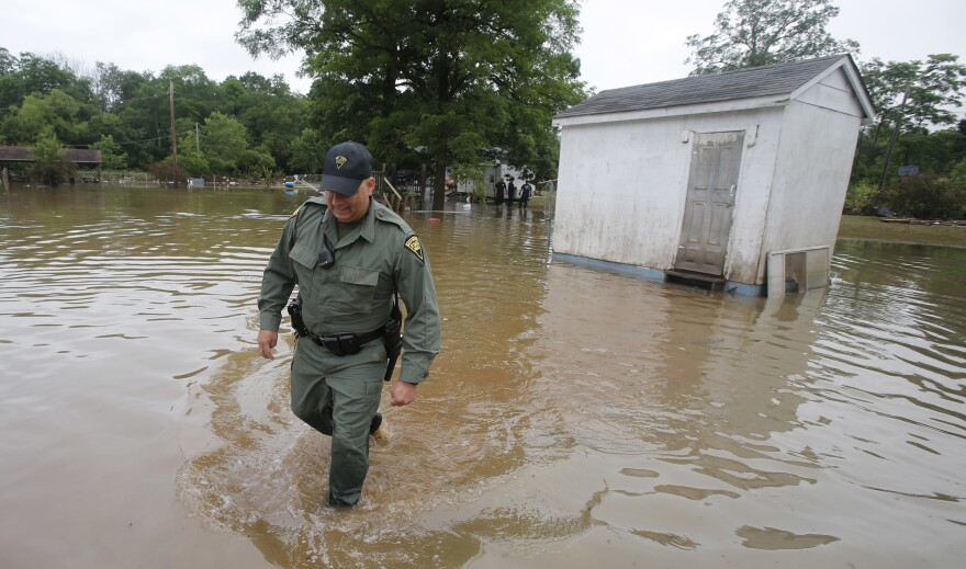 West Virginia State Trooper C.S. Hartman walks from a shed that he checked out as he and other crews search homes on Saturday in Rainelle, W.Va.