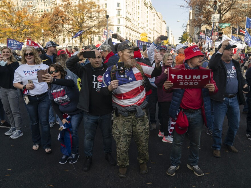 Supporters of President Trump cheer as his motorcade drives past a rally in downtown Washington, D.C. to challenge the outcome of the 2020 election.