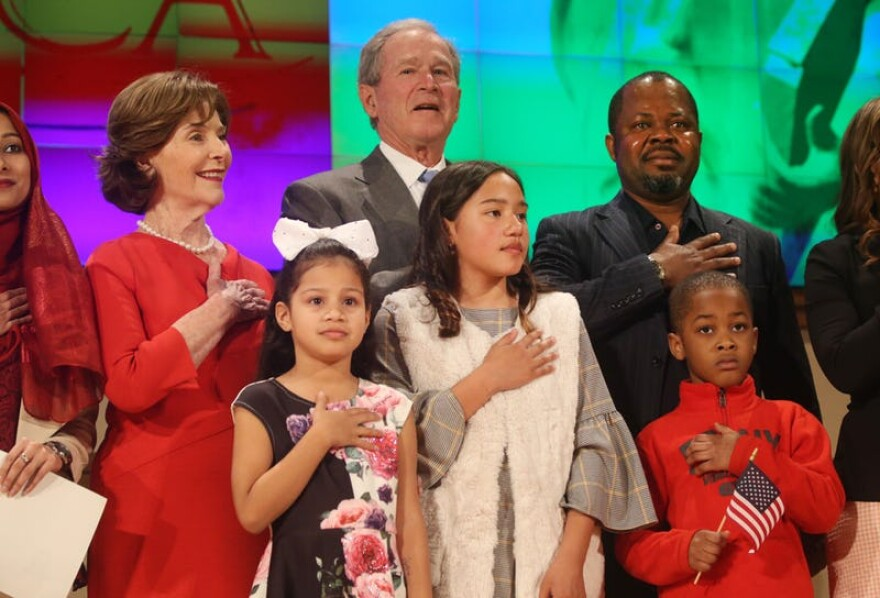 Former President George W. and Laura Bush recite the pledge of allegiance with new U.S. citizens including Felix Odeh (top right) of Nigeria, during a naturalization ceremony at the George W. Bush Presidential Center in Dallas on Monday.