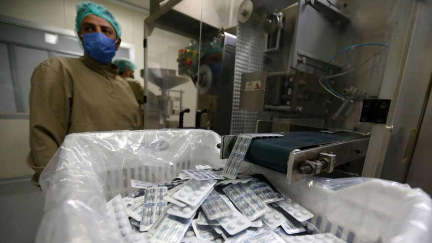 An employee of a Syrian pharmaceutical factory works on the production line of the hydroxychloroquine drug on April 28, in the government-controlled city of Homs.