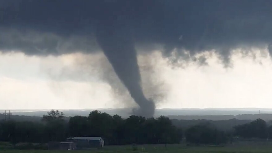 "This image, made from a video taken through a car window, shows a tornado near Wynnewood, Okla., on Monday. A broad tornado capable of leaving ""catastrophic"" damage in its wake churned across the Oklahoma landscape Monday, prompting forecasters to declare a tornado emergency for two communities directly in its path."