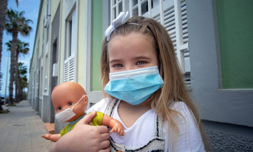 Naidelin, 5, and her doll pose wearing a face mask in the street in Santa Cruz on the Canary Island of Tenerife, on April 26, 2020 during a national lockdown to prevent the spread of the COVID-19 disease.(DESIREE MARTIN/AFP via Getty Images)
