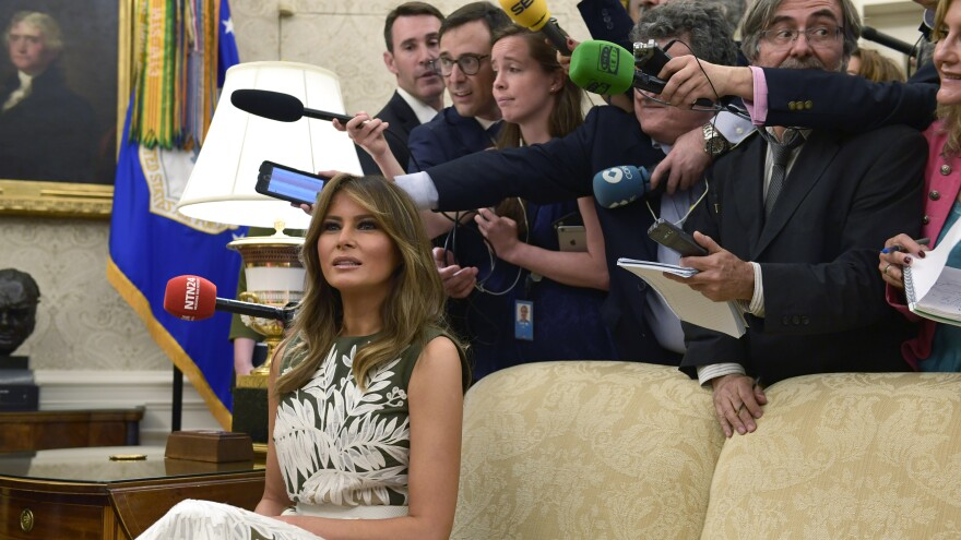 First lady Melania Trump sits on a couch surrounded by reporters as she participates in a meeting with President  Trump, Spain's King Felipe VI and Queen Letizia in the Oval Office on Tuesday.