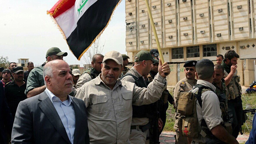 Iraqi Prime Minister Haider al-Abadi (left) tours Tikrit after it was retaken by security forces who drove out Islamic State fighters on April 1. Shiite militias allied with Iraqi government troops were accused of committing human rights abuses as they helped retake the city.