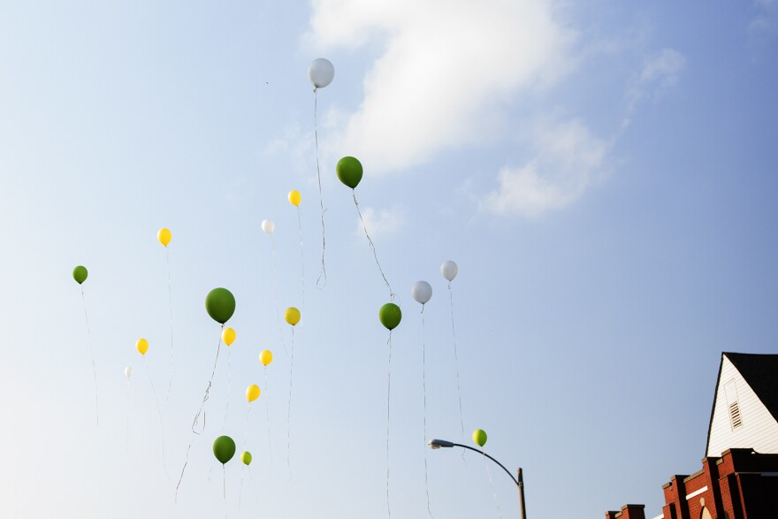 The crowd releases balloons that reflect Dunbar's school colors.