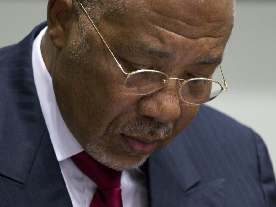 Former Liberian President Charles Taylor takes notes during his trial Thursday. He was found guilty of aiding war crimes in Sierra Leone.