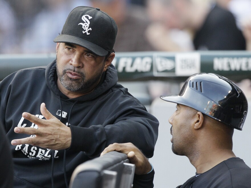 Chicago White Sox manager Ozzie Guillen, left, talks with first base coach Harold Baines in the dugout during a game in 2011.