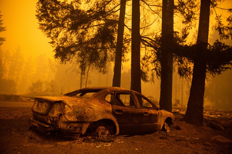 The charred husk of a car remains after the Santiam Fire moved through a neighborhood Wednesday near Gates, Ore.