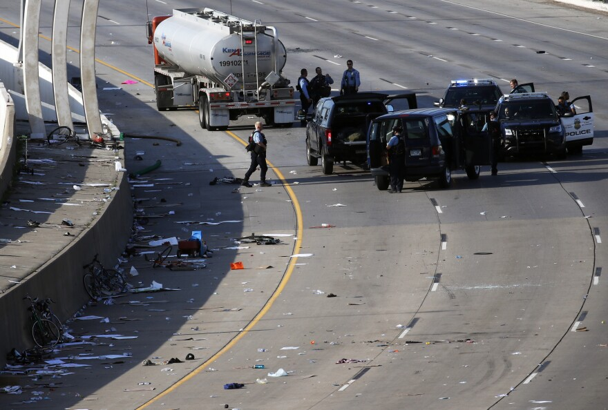 Police clear the area where a semitrailer rushed to a stop among protesters on an interstate highway on Sunday in Minneapolis.