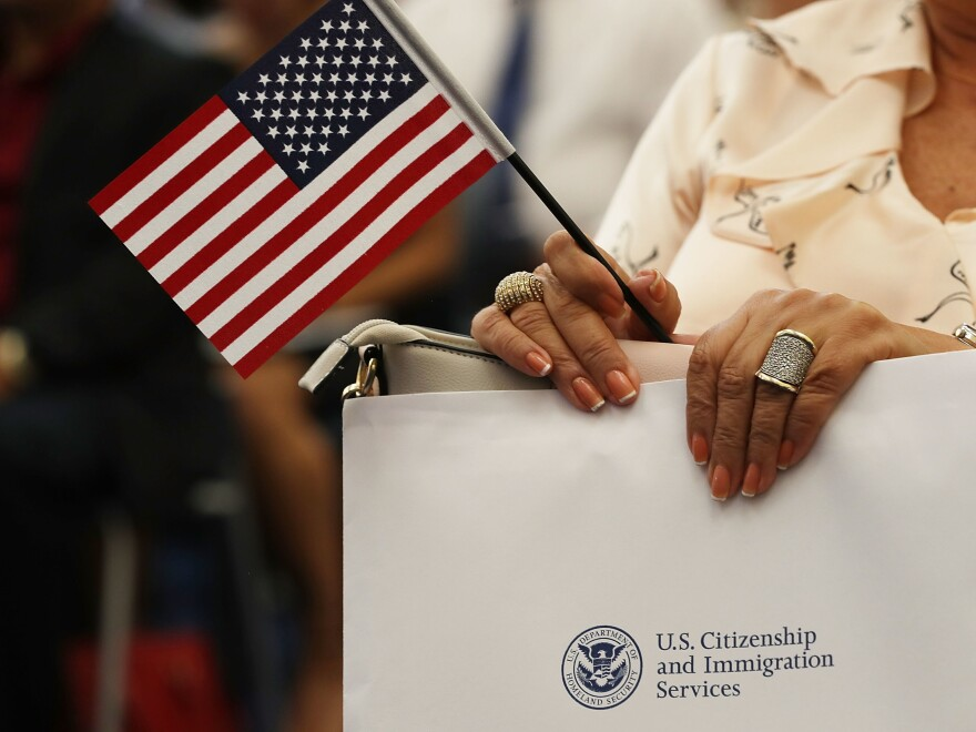 An attendee holds an American flag at a U.S. Citizenship & Immigration Services naturalization ceremony in Miami, Fla. in Aug. 2018. The Trump administration is considering expanding its collection of biometric data as part of the immigration process.