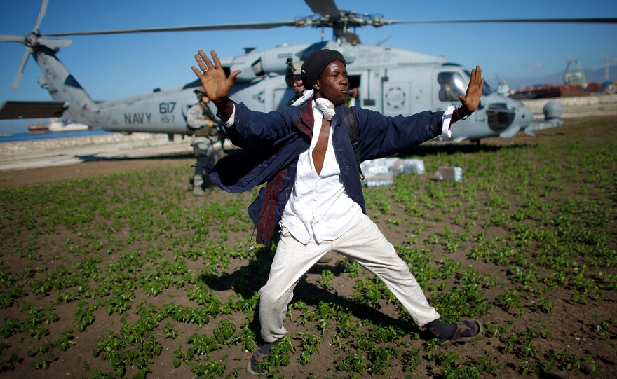 A Haitian man tries to keep a crowd of people from rushing a U.S. Navy helicopter as it touches down to drop off water in downtown Port-au-Prince on Jan. 16, 2010.