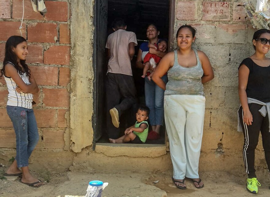 Raquel Castaño stands to the right of the entrance to her home in Ramo Verde, a poor neighborhood on the outskirts of Caracas, Venezuela, is a mother of five. She says her 15-year-old son often skips school to work delivering water to the community.