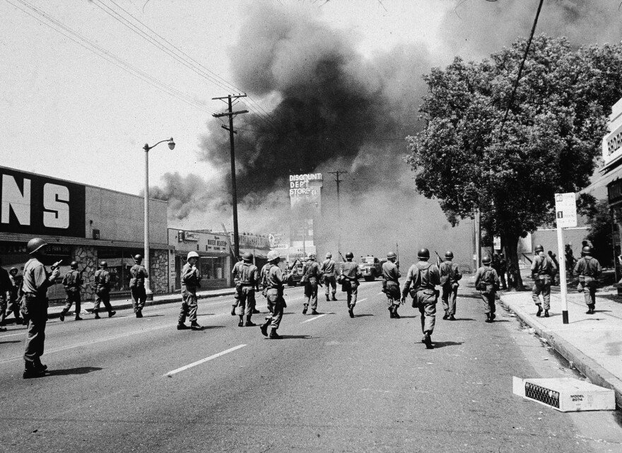 Armed National Guardsmen march toward smoke of street fires during the Watts riots in Los Angeles in 1965. The unrest was initiated when a California Highway Patrol officer stopped a black driver.