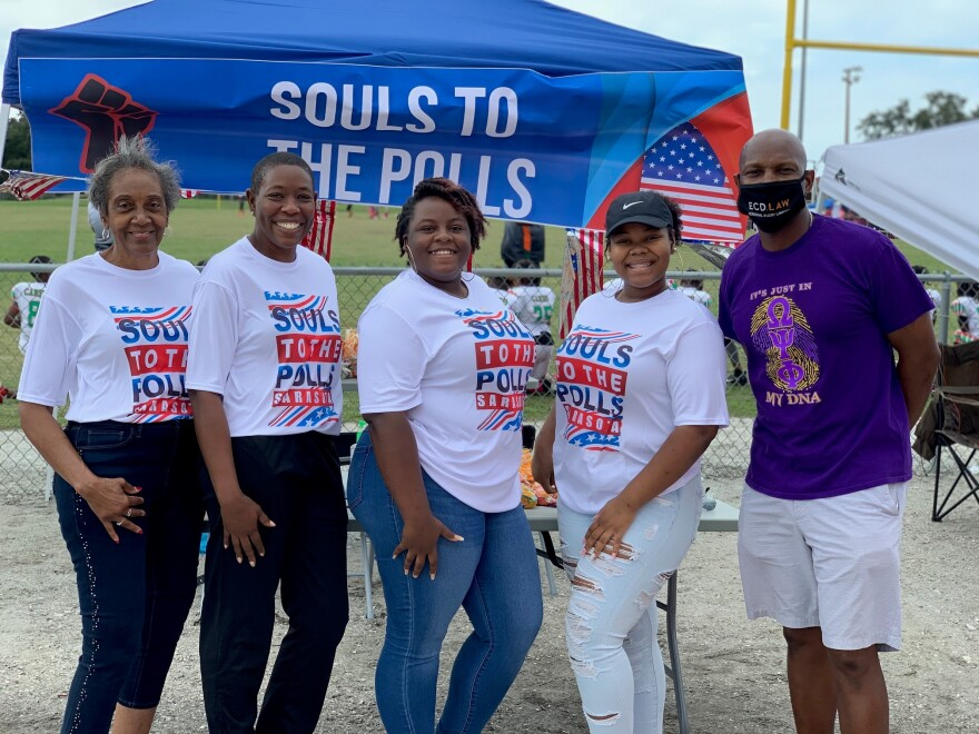 Five people stand in front of tent wearing Souls to the Polls t-shirts