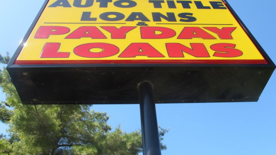 A bright yellow sign for a loan store advertises auto title loans and payday loans.